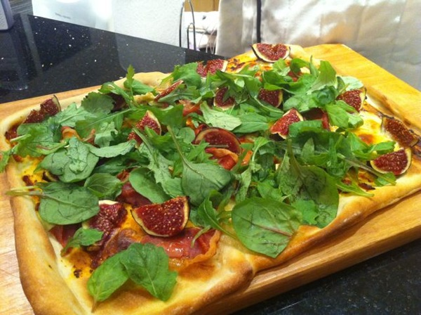 Homemade Pizza dough with prosciutto, figs and rocket topping