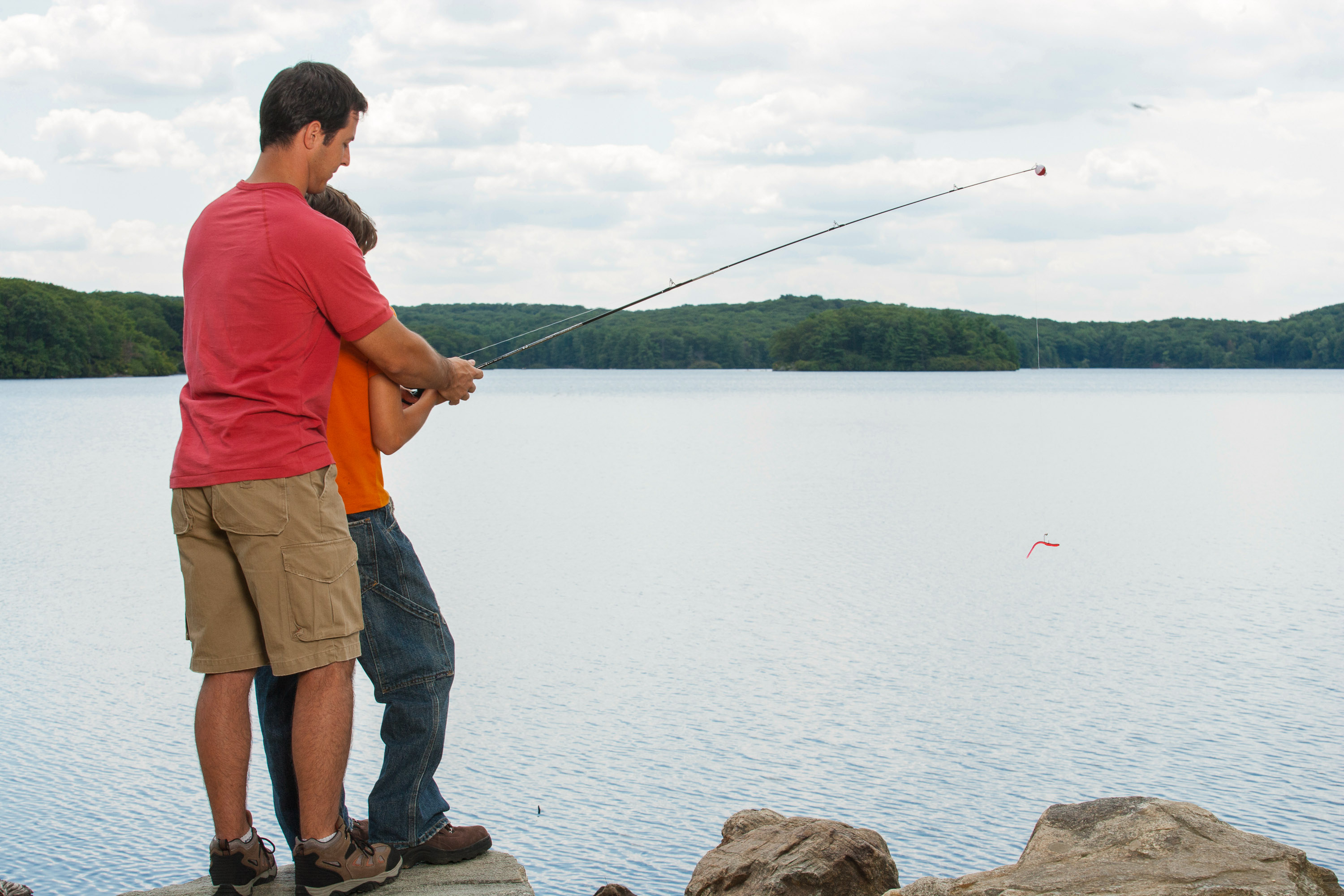 Father and son fishing at lake together