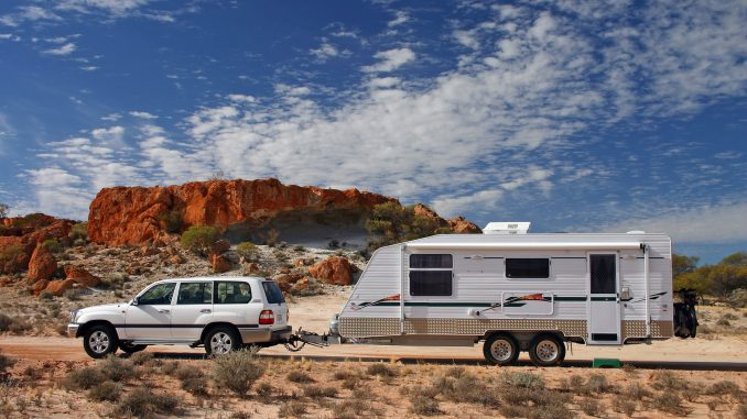 Four wheel drive and offroad caravan in outback Australia against a stunning red rock outcrop with an deep blue sky and interesting cloud formations