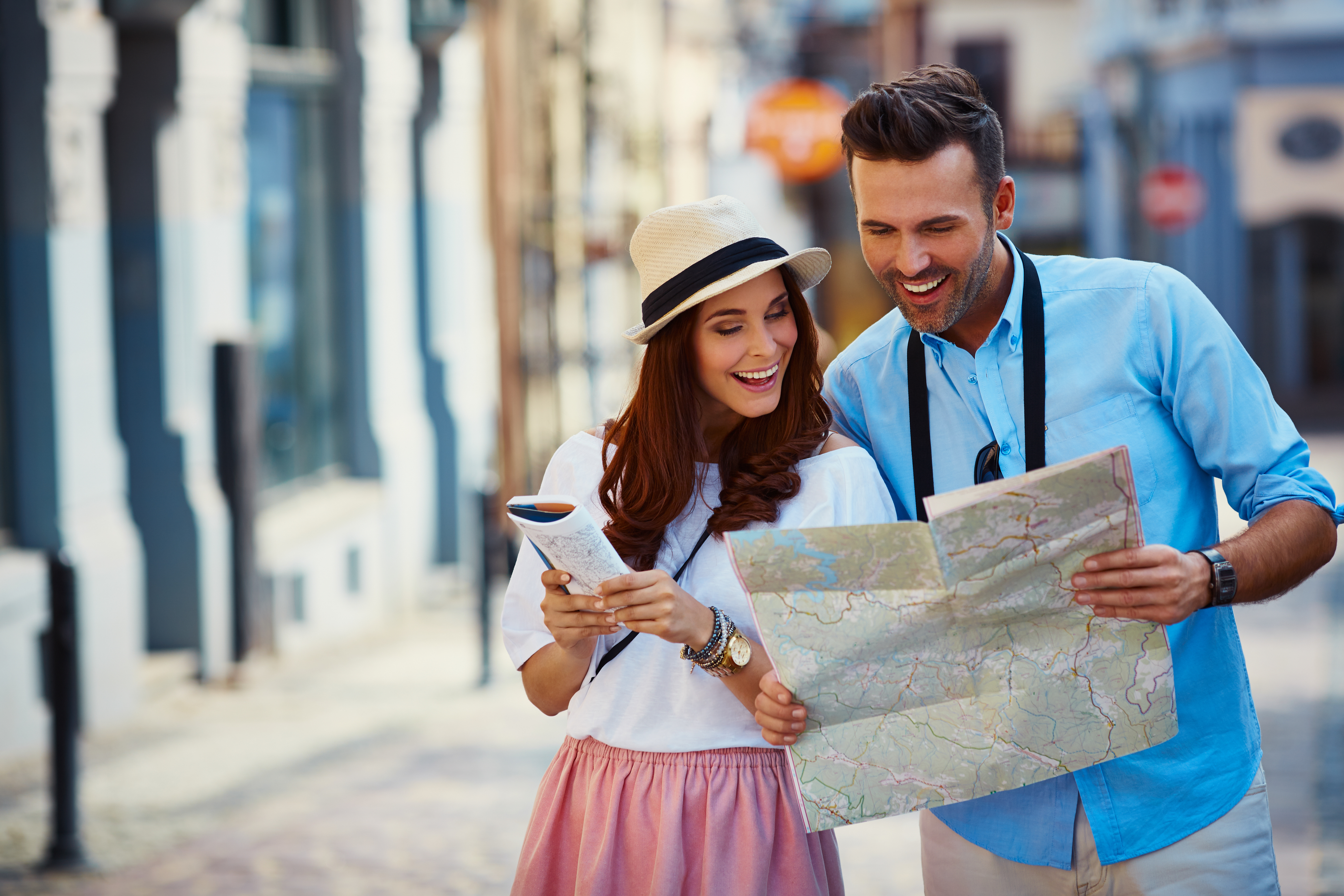 Young couple traveling, reading map in the city